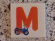 Part No: 3068bpb0722  Name: Tile 2 x 2 with Groove with Letter M Red with Motorcycle Pattern