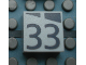 Part No: Mx1022Apb189  Name: Modulex, Tile 2 x 2 with Dark Gray Slopes and Calendar Week Number '33' Pattern